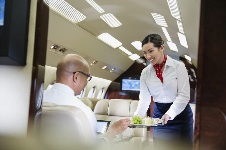 Flight attendant serving passenger