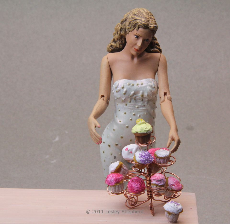 Miniature cupcakes on a wire cupcake stand in dollhouse scale.