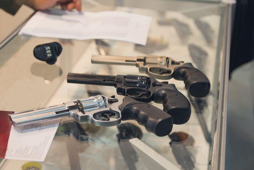Handguns on a counter in a shop.
