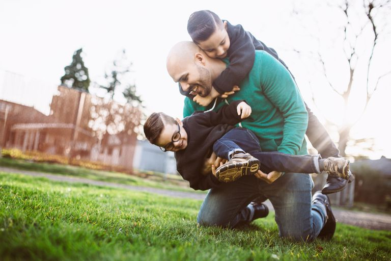 Father wrestling kids in the yard