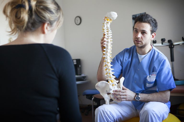 A physiotherapist holding spine model