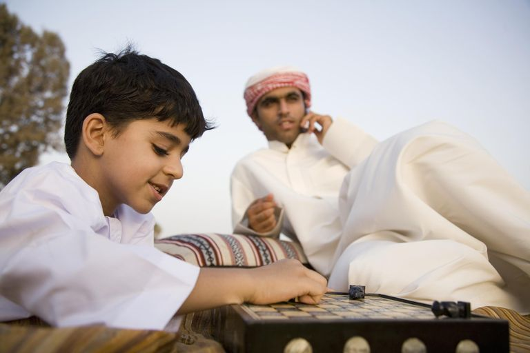 Son playing board game in park, with Father talking on phone, Dubai, UAE