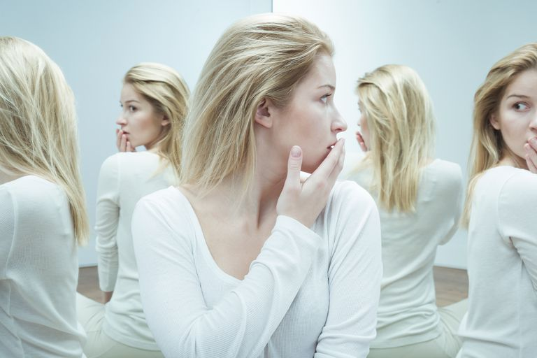 woman in the mirror appearing frightened