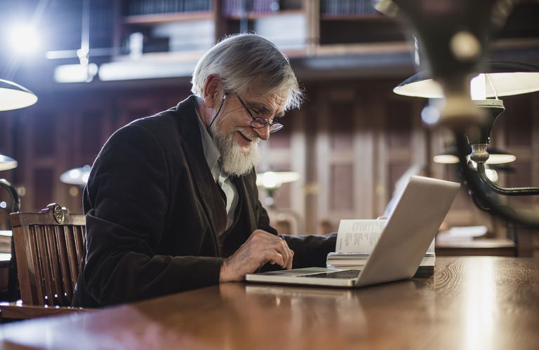 Senior Man Sitting in the Library and Using Laptop