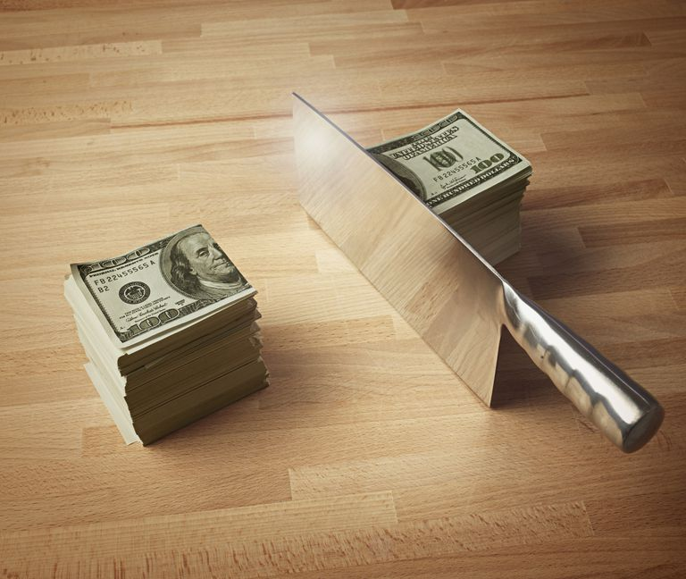 Stack of money cut in half by a cleaver