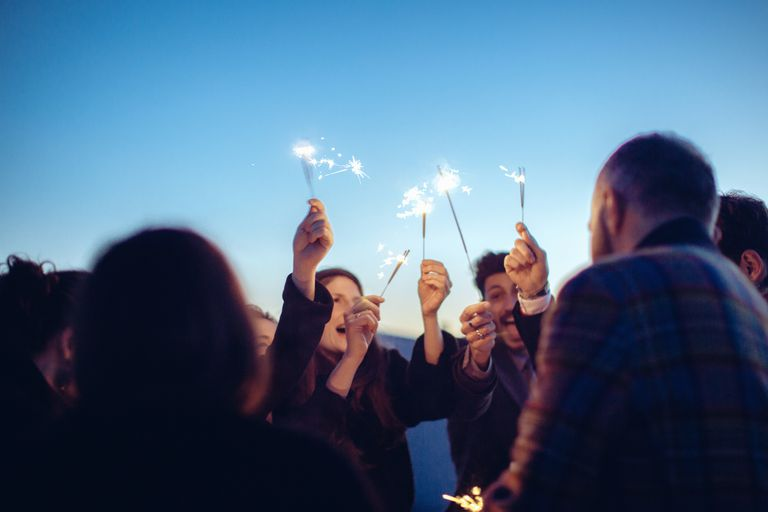 Group of friends holding sparklers in air, at party