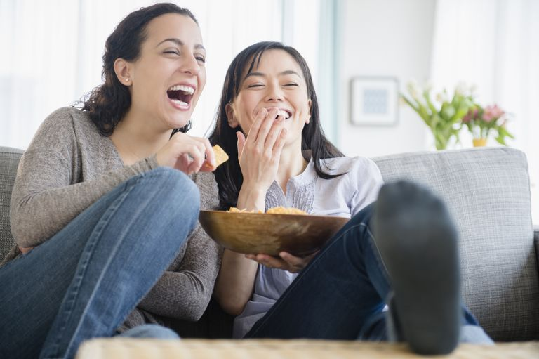women watching a comedy together during the two week wait, using distraction to cope