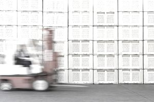 Person driving forklift beside stack of crates