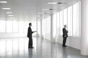 Letting agent showing businessman around empty office