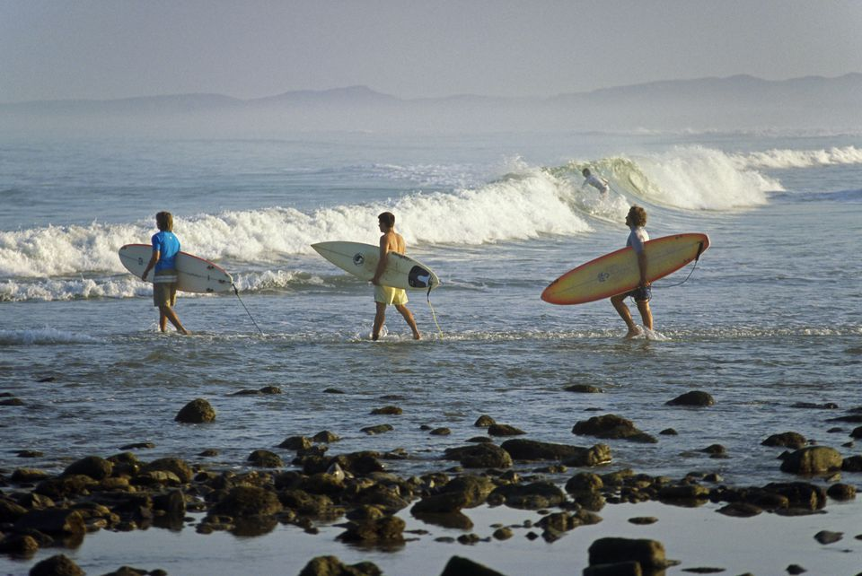 Surfers head into the surf at Mancora on the northern coast of Peru. The beach resort close to the Ecuadorean border is a popular destination for holidaying Peruvians