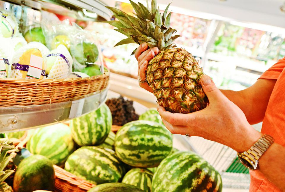 Man choosing pineapple at the grocery store