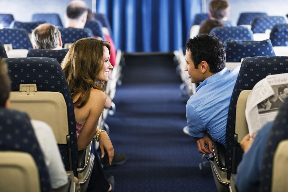 Man and woman talking over airplane isle