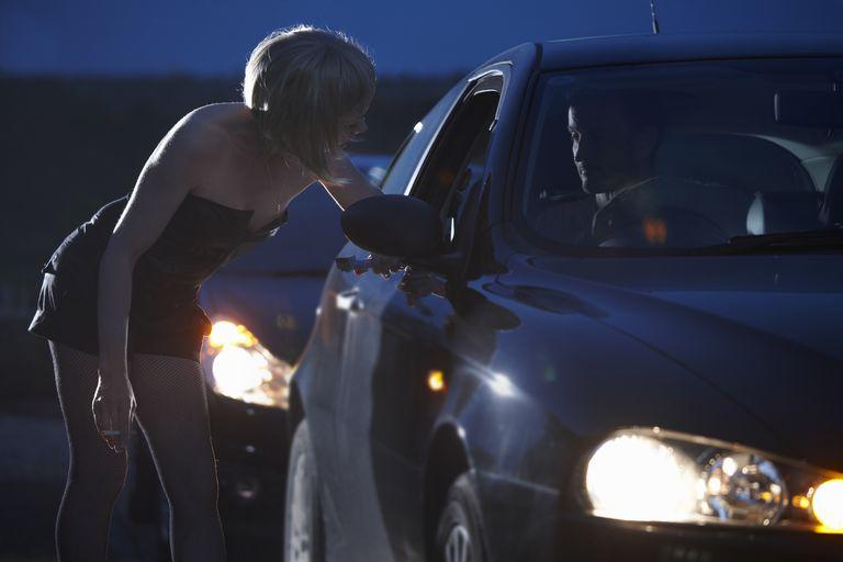 motorist talking to prostitute in street at night