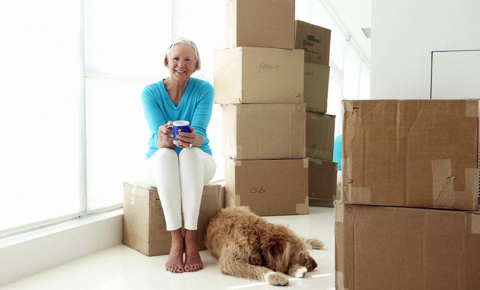 Senior woman with her dog sitting on a packed box