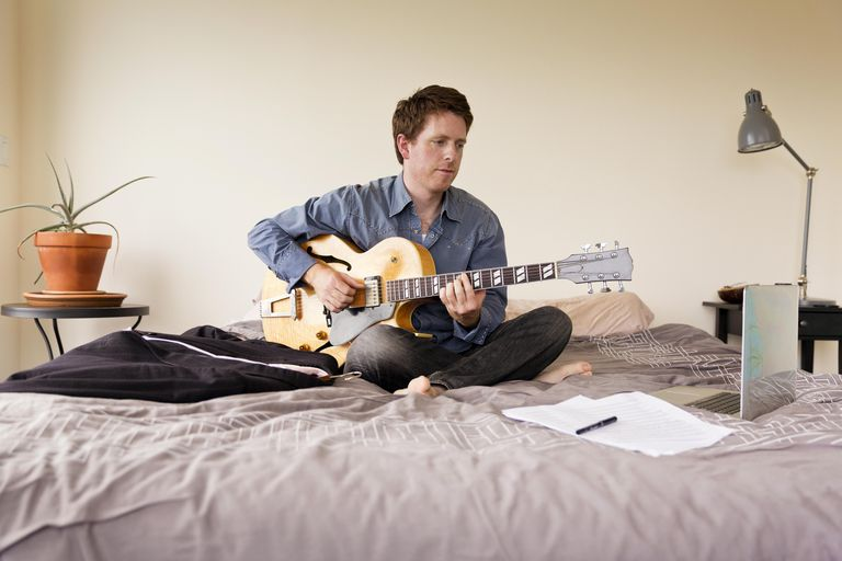 Guitarist Practicing Music on Bed with a Laptop