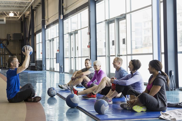 Instructor guiding exercise class at gym