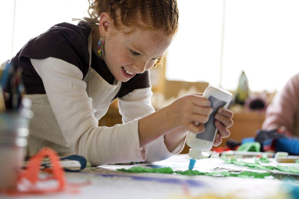 Girl applying glue to craft