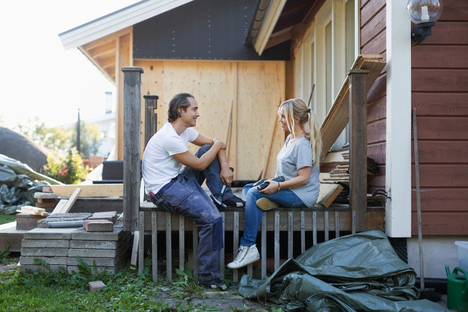 Happy couple looking at each other while renovating house
