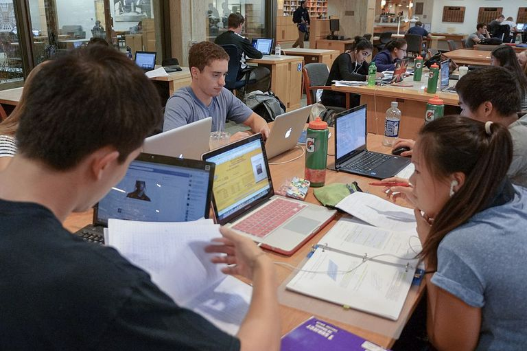 Multiple groups of college students sit together at tables in the Milton S Eisenhower Library at Johns Hopkins University, studying from notebooks and laptops, with water bottles and papers scattered across the tables, Baltimore, Maryland, 2014