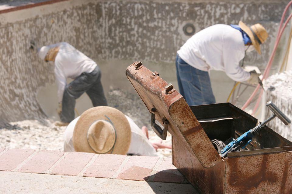 Workmen repairing a pool