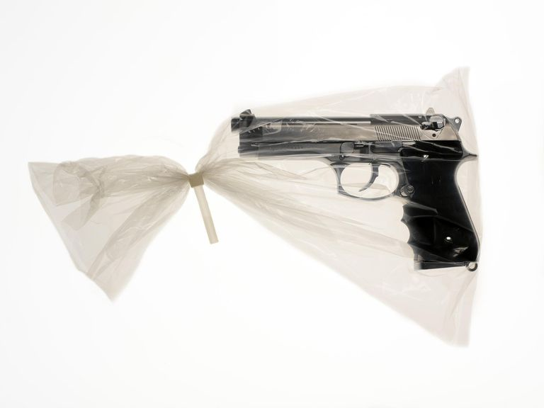 Handgun in plastic bag sealed with unreasonable plastic tie, close-up