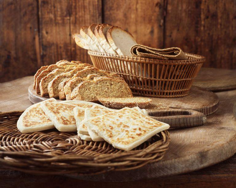 Irish flatbread, soda bread and white sliced bread on wooden cutting boards