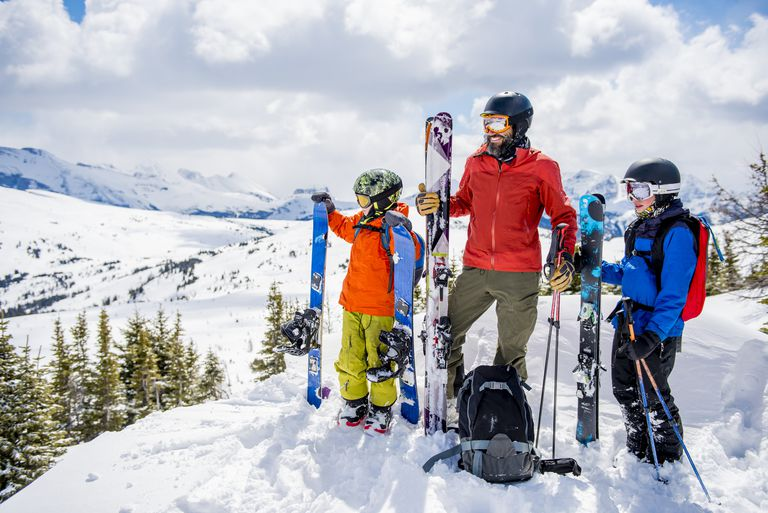 Father and sons relax in fresh snow, with skiis