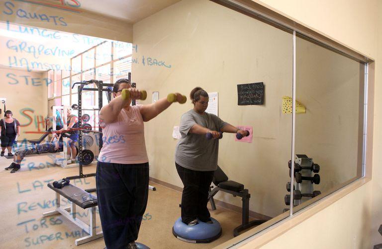 2 overweight women lifting weights