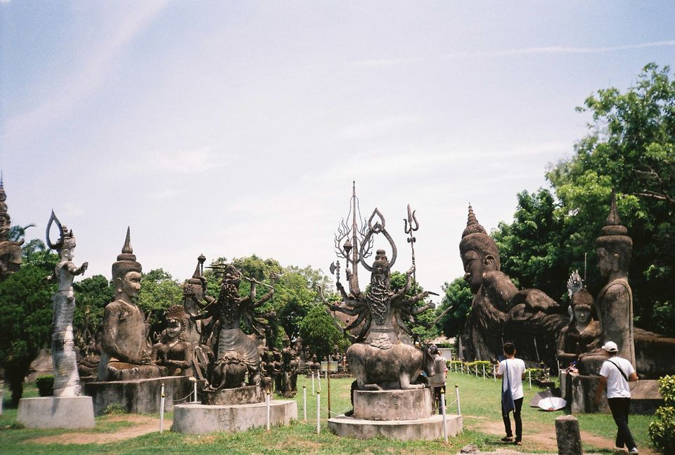 Rear View Of Tourists Visiting Wat Xieng Khuan Against Sky
