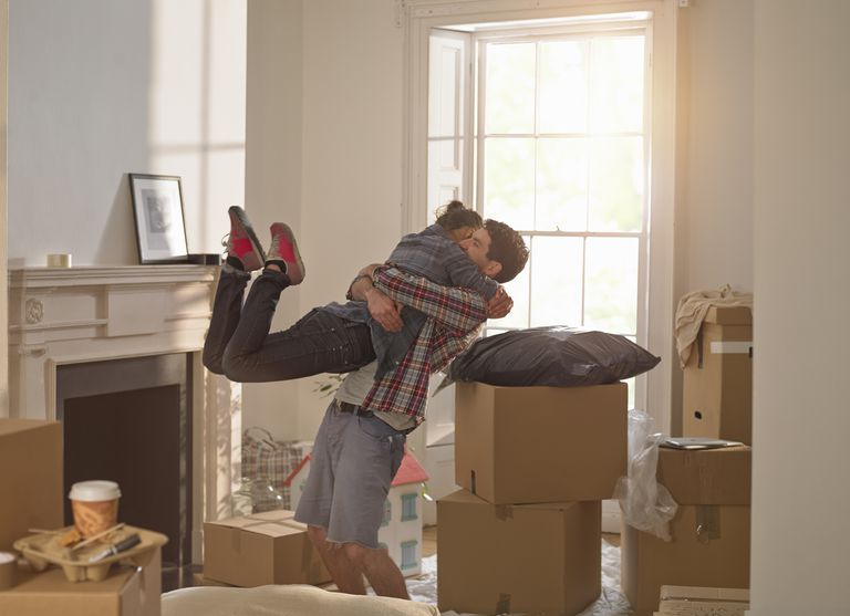 couple hugging in new home with boxes around