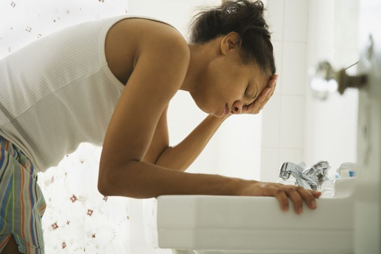 Woman leaning over the sink with her head in her hand, disappointed she got her period when she wanted to be pregnant