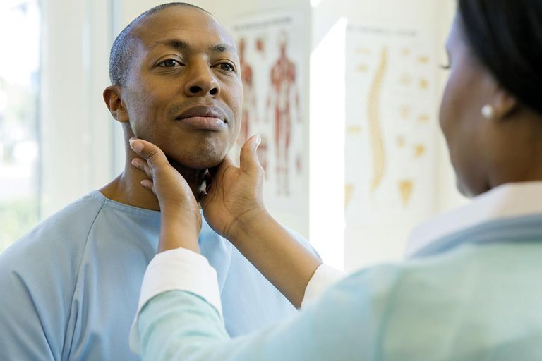Female doctor examining male patient's glands in clinic