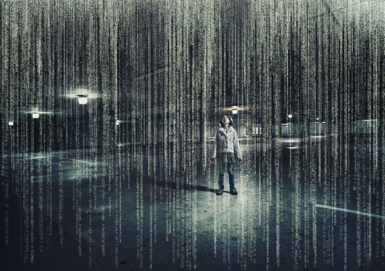 Mixed race girl standing in parking lot under raining binary code