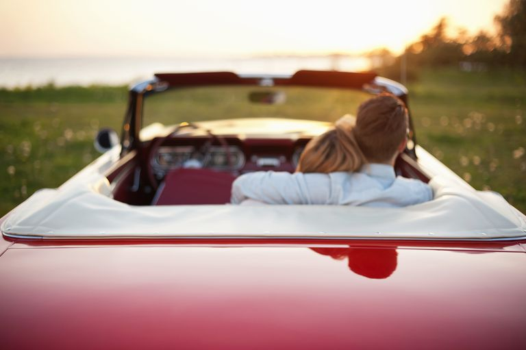Rear view of young couple with arms around sitting in convertible car at field