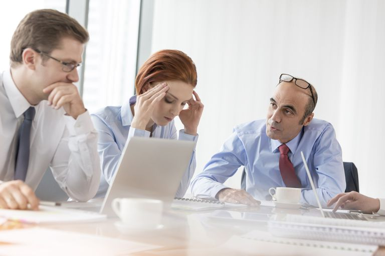 man talking to two tense colleagues in meeting