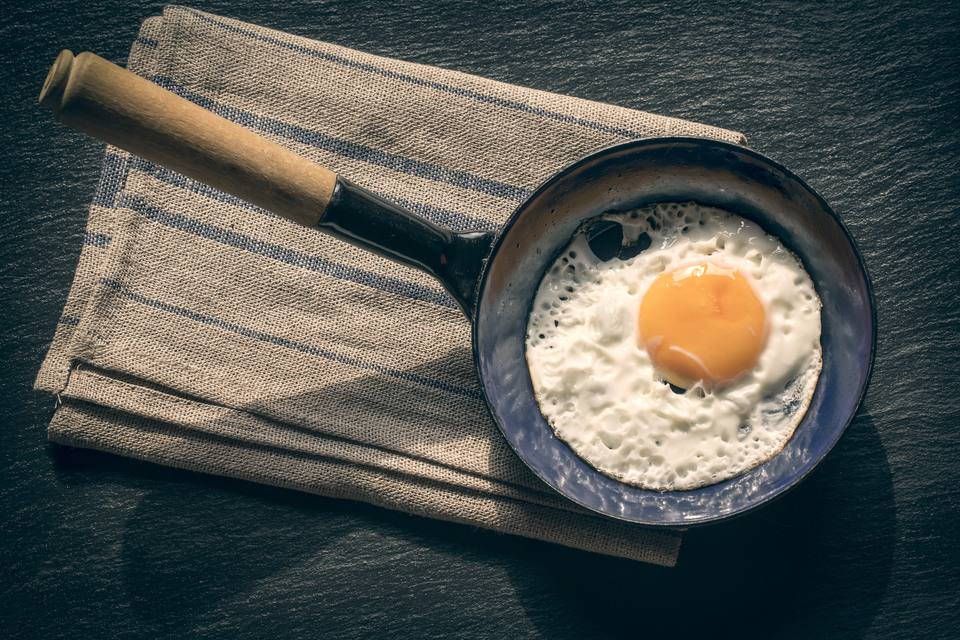Fried egg in pan and tablecloth