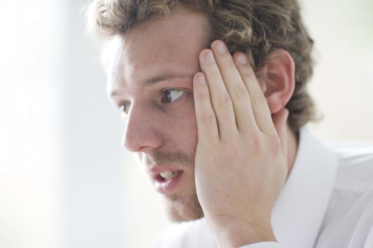 Close up of young businessman with hands on face