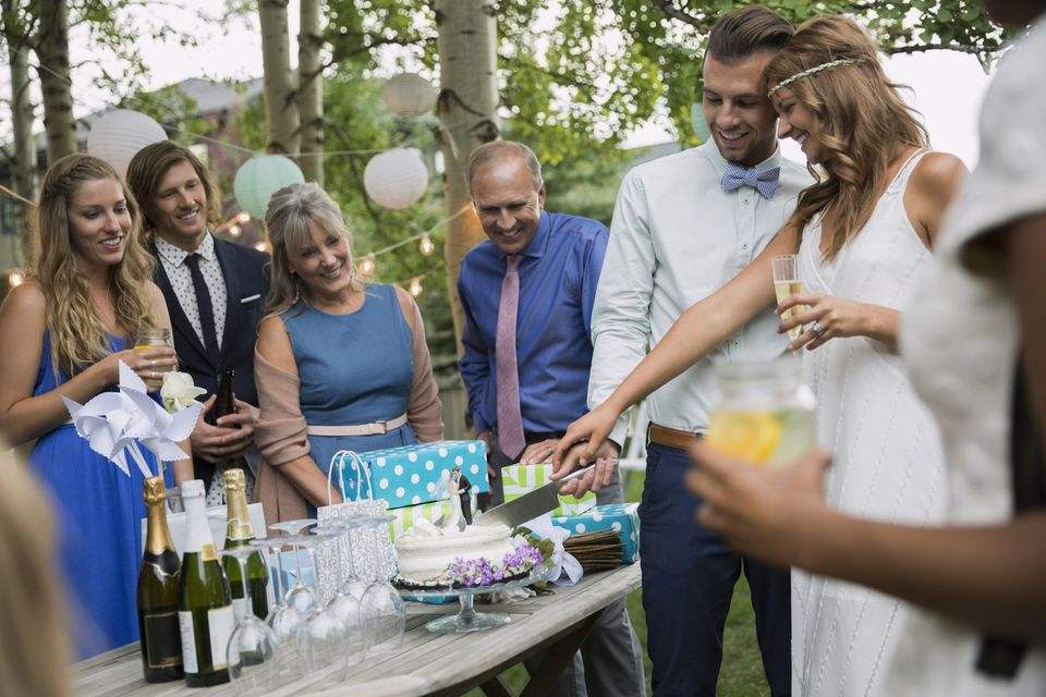 Bride and groom cutting cake backyard wedding reception