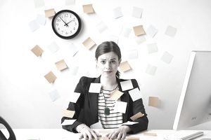 Woman with sticky notes of to dos posted all over herself and the wall
