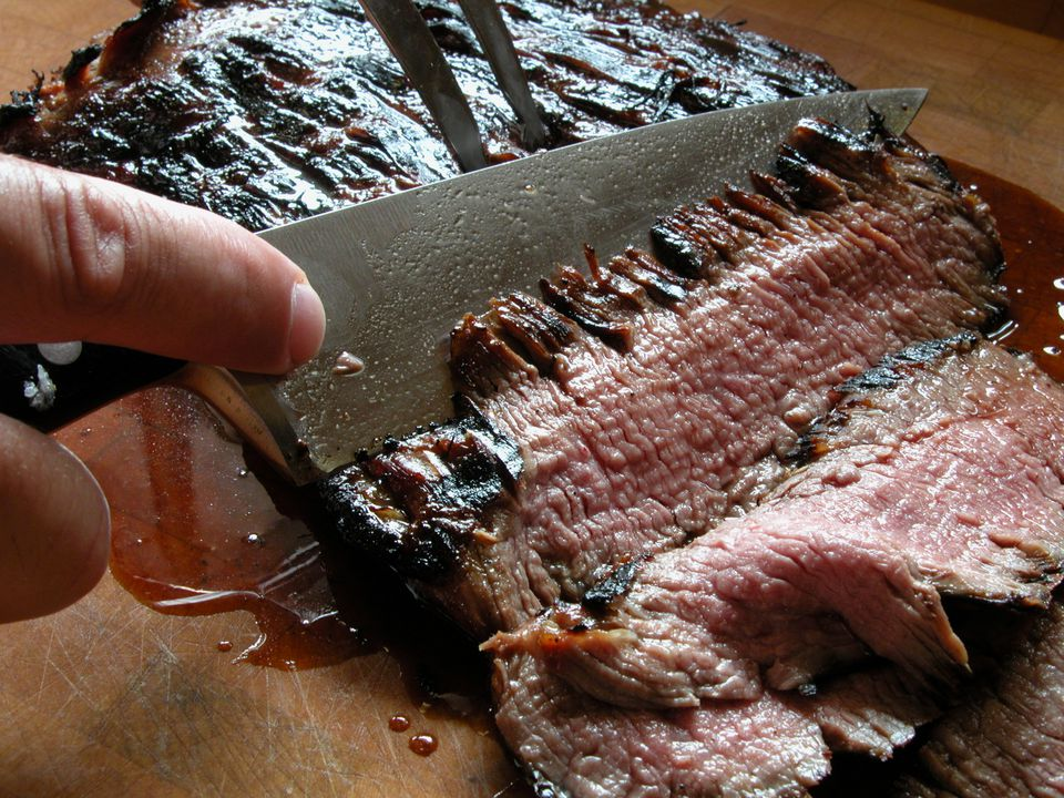 Close-up of a knife carving a piece of grilled flank stake