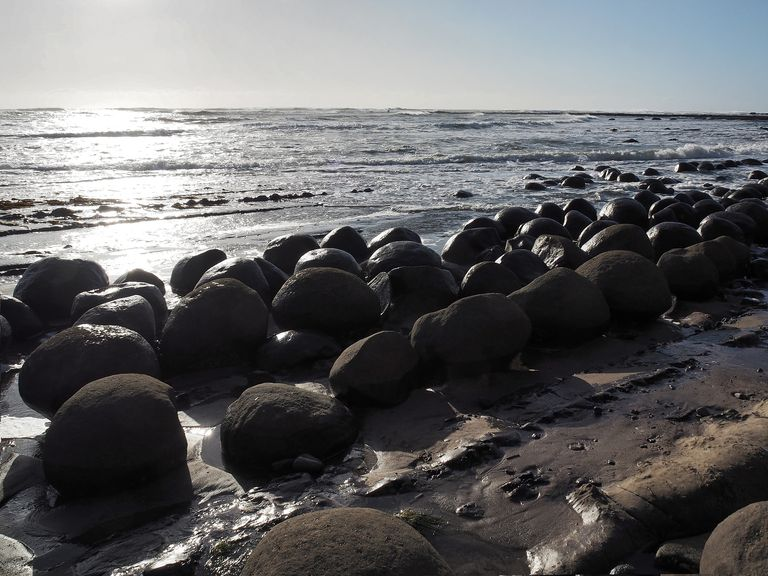 Backlit View Of Spherical Rock Concretions At Bowling Ball Beach, California