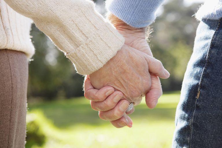 Older couple holding hands.