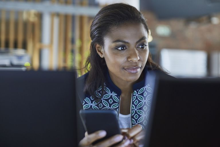 Businesswoman texting at computer in office