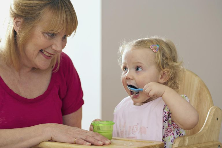 Grandmother sitting beside granddaughter in high chair and holding pot whilst her granddaughter feeds herself from a blue plastic spoon