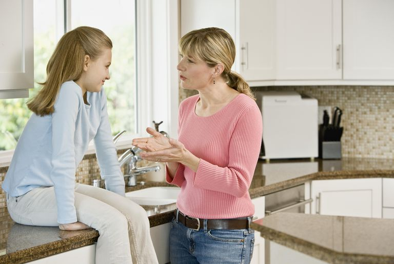 Mother and daughter (10-11) discussing in kitchen