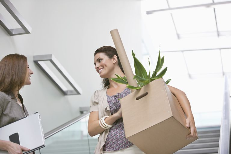 Woman with cardboard box talking to colleague