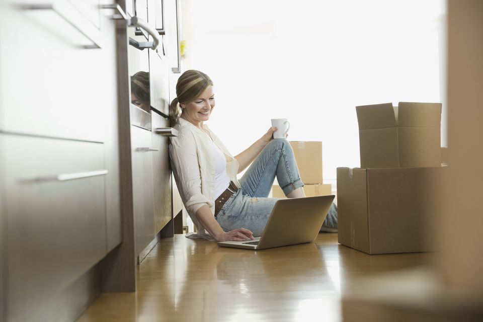 Woman using laptop on floor near moving boxes