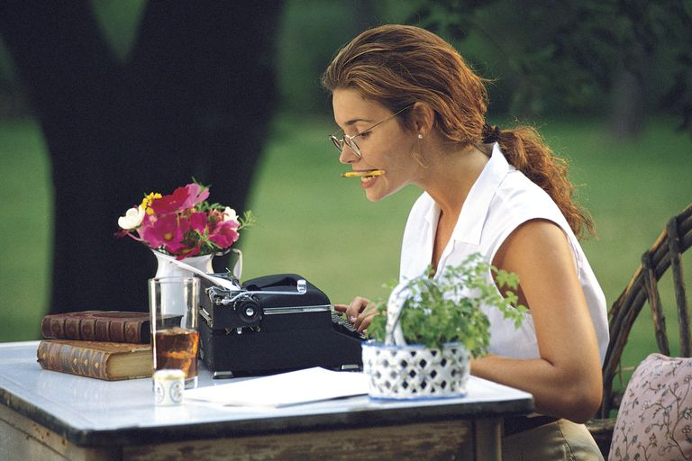 Young woman concentrating on writing a letter on a typewriter outdoors.
