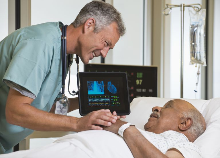 Doctor speaks to patient in bed hooked up to heart monitor