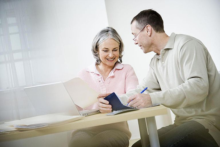 Mature couple doing paperwork using laptop